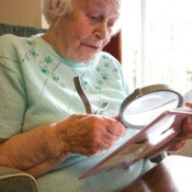 Senior woman using a large magnifying glass to read.