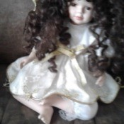 Value of Porcelain Doll - doll with long curly hair wearing a flower wreath