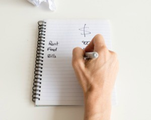 Writing a budget on a notepad.