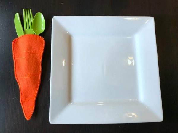 Felt Carrot Utensil Holder - carrot utensil holder next to square white plate