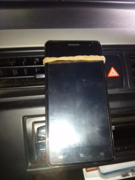 A cellphone in a car, being held by a rubber band.