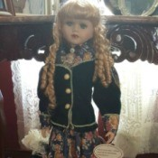 Value of Porcelain Doll - blond doll with ringlets, wearing long floral skirt and buttoned jacket