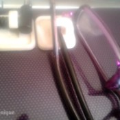 Cords and eyeglasses hanging on Command hooks on the side of a laptop.