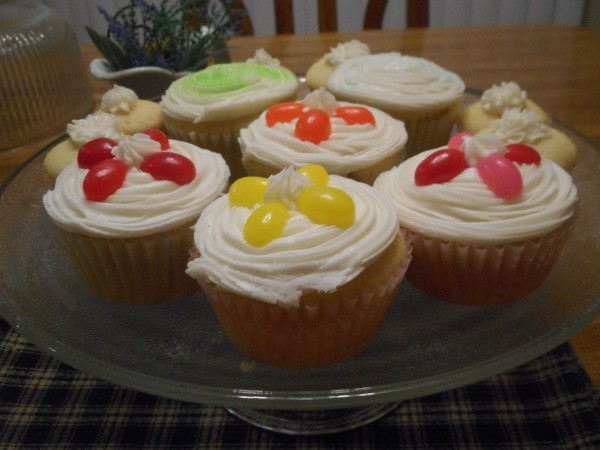 Cupcakes with jellybeans decorating the tops in a flower pattern.