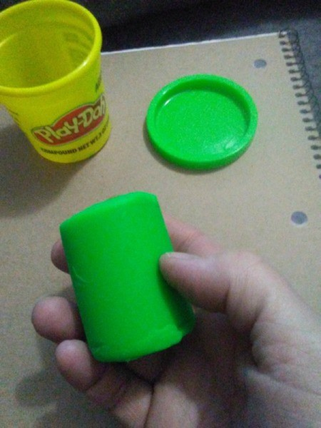 Mod Podge to Preserve Play Doh Creations - hand holding a piece of green Play Doh