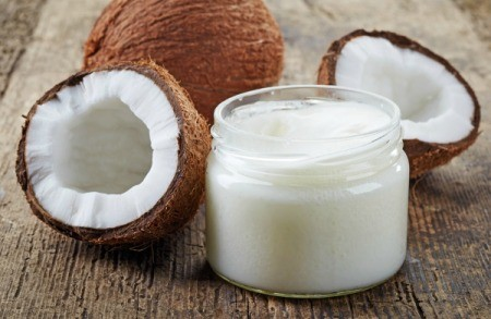 A jar of coconut oil next to a cracked coconut.