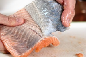 A person removing the skin from a salmon filet.