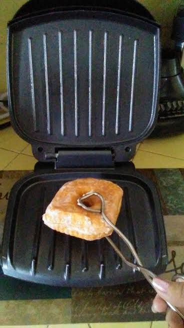 Placing a glazed doughnut on an electric grill.