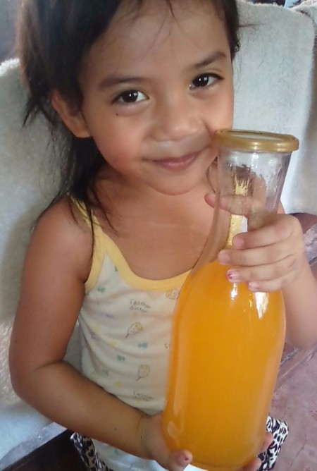 A child holding a glass bottle of juice.