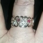 A gold and gemstone ring on a woman's finger.