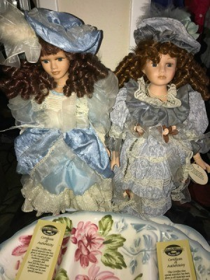Two porcelain dolls with brown curls and blue and white dresses.