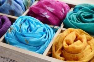Several colorful silk scarves in a divided box.