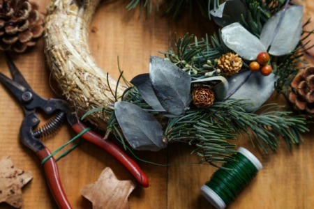 A handmade wreath being assembled, with tools and materials.