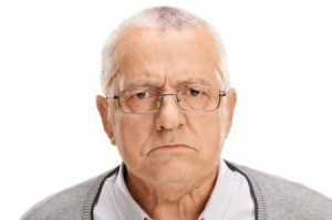A grouchy old man with a frown on his face.