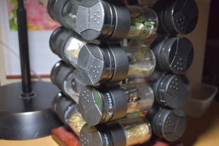 A spice rack being used to organize seeds.
