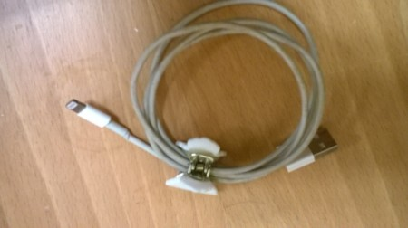 A looped computer cord being held together with a hair clip.