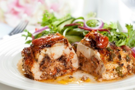 A stuffed chicken breast on a plate with salad.