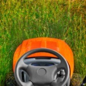 A riding lawnmower, from the view of the seat.