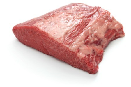 An uncooked beef brisket on a white background.