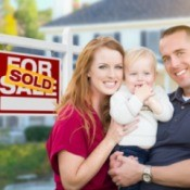 A happy couple with a baby outside a home with a for sale sign, marked sold.