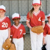 A children's baseball team with red tops and white pants.