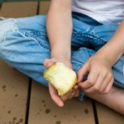 A child sitting cross-legged with holes in the knees of her pants.