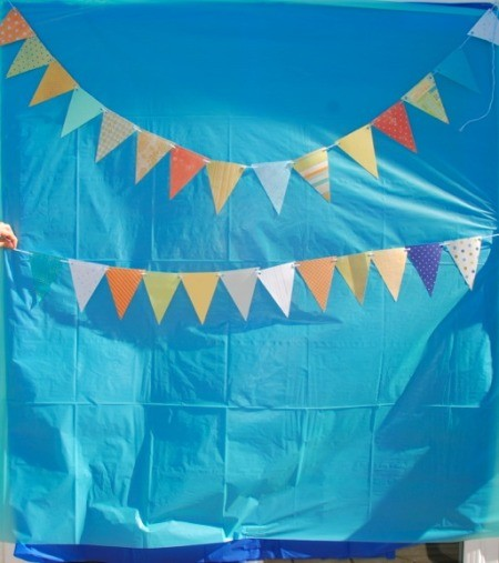 A background placed on a wall with bunting to be used as a photo booth.