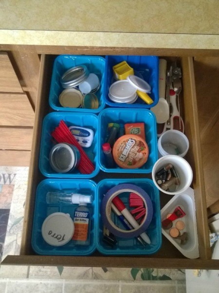 An organized junk drawer using recycled containers as dividers.