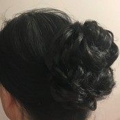 An updo wrap attached to black hair.