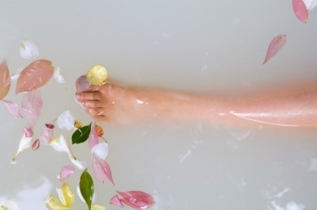 A lower leg in a bathtub, filled with milk and flowers.
