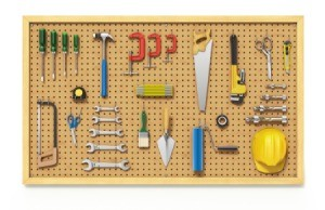 A pegboard with tools hanging on it.