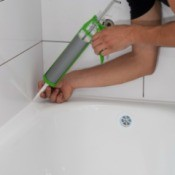 A person caulking around a bathtub.