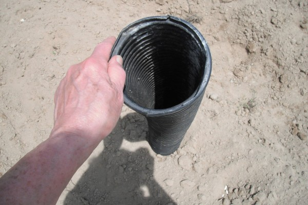 A long pipe pointing to the ground, for use in planting seeds.