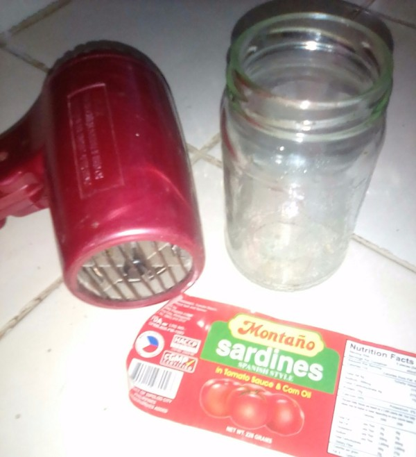 A label removed from a glass jar, next to the jar and a hair dryer.