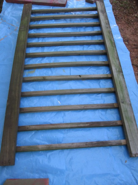 Old Deck Railing Used For Garden Tool Storage - railing on blue tarp ready for painting