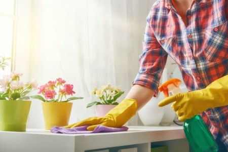 A woman spraying cleaner on a white counter.