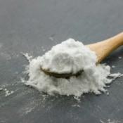 A white powder on a spoon, either baking soda or baking powder.