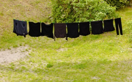 A row of black clothing on a clothesline.