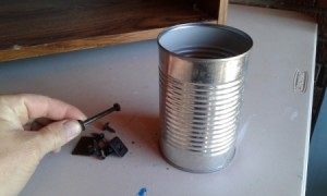 A recycled aluminum can for storing nails and other hardware.