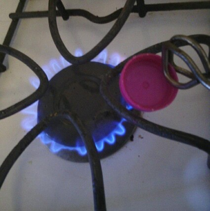 Plastic Bottle Cap Nozzles  - heating cap over the flame of a gas stove