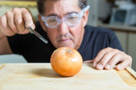 A man wearing swimming goggles while cutting an onion.