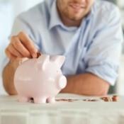 A man putting change into a small piggy bank.