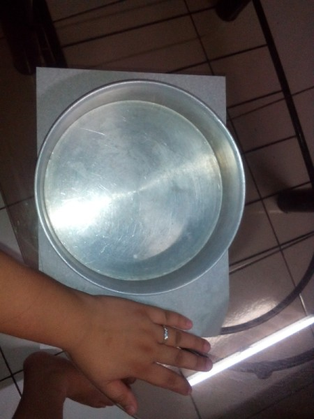 Cutting wax paper to fit in a round pan.