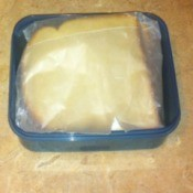 A sandwich wrapped in wax paper and then stored in a plastic container.