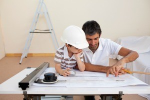 A boy at work with his father, looking at blueprints.