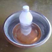 A frozen water bottle in a pet's water bowl.