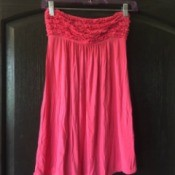 A skirt hanger holding a strapless dress.