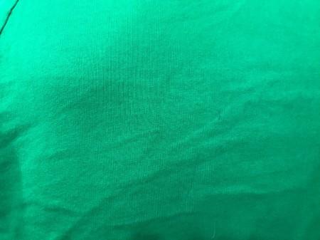 A green sweatshirt with very faded pen markings.