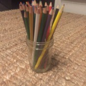 A mason jar used to store colored pencils.