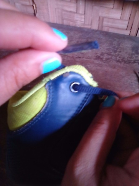 A repaired shoelace being inserted into the eyelet of a pair of shoes.